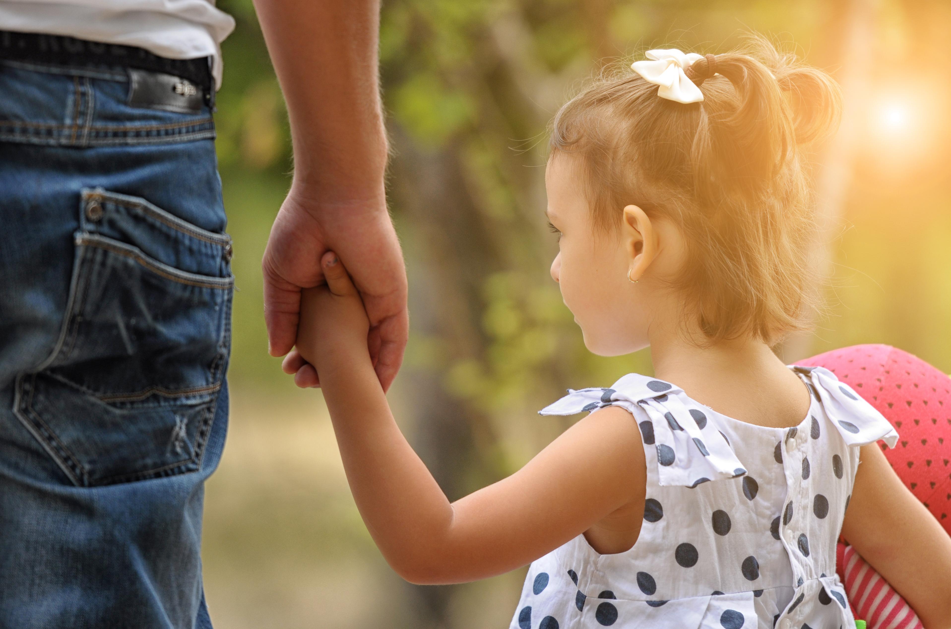 Padre llevando a su hija adoptada de la mano