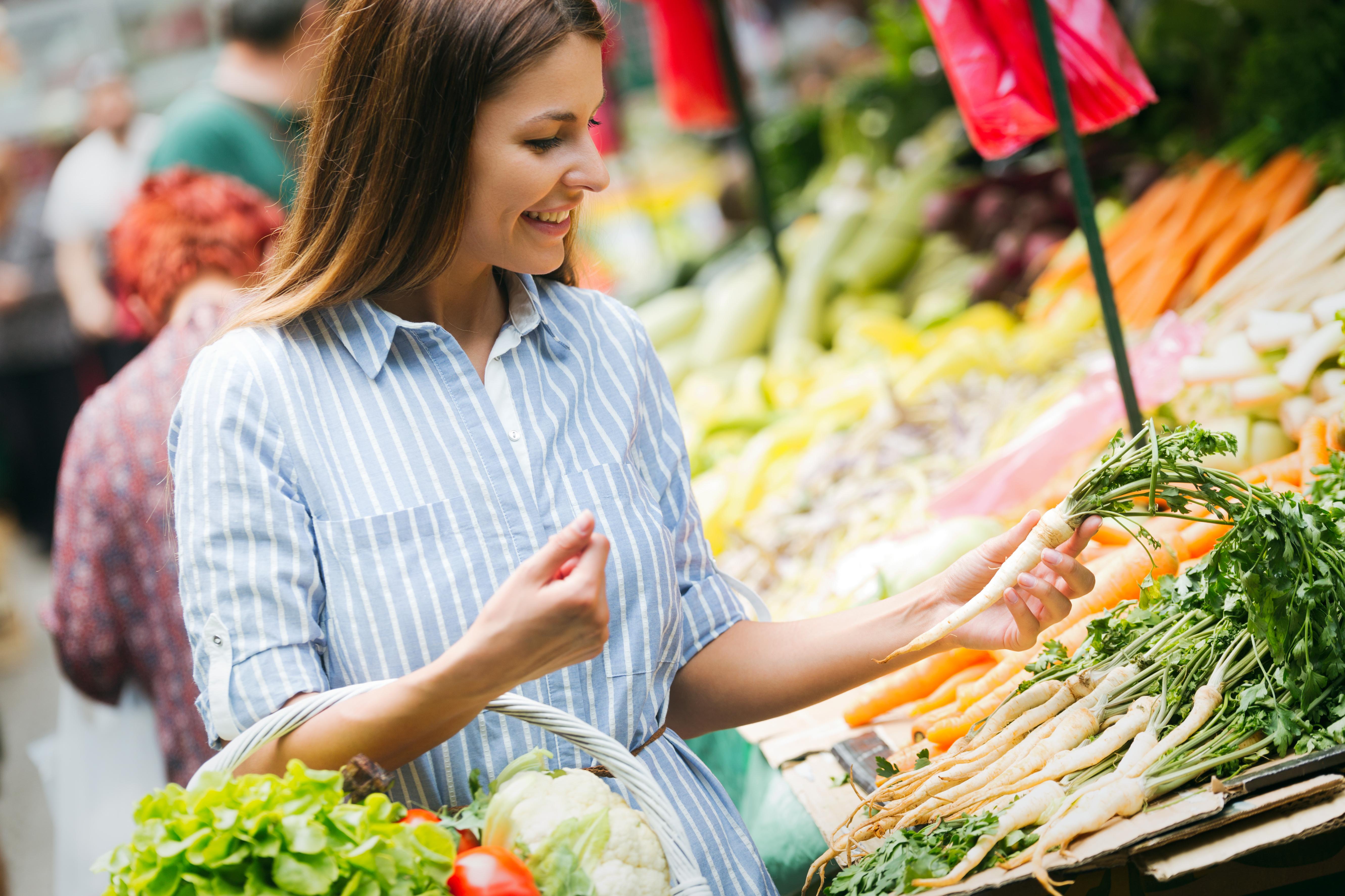 Mujer en edad fértil comprando verduras en el mercado
