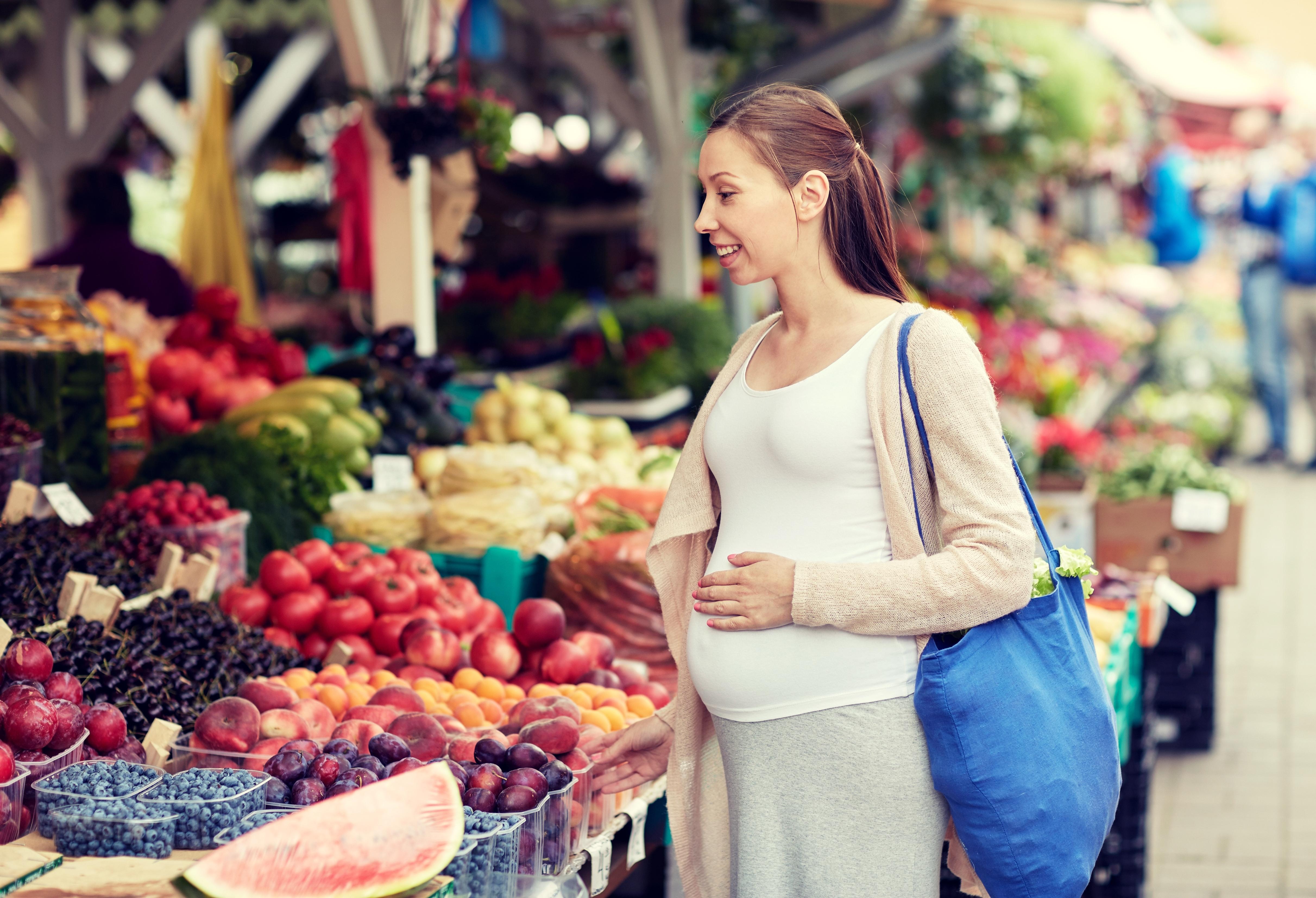 Mujer embarazada comprando fruta y verdura