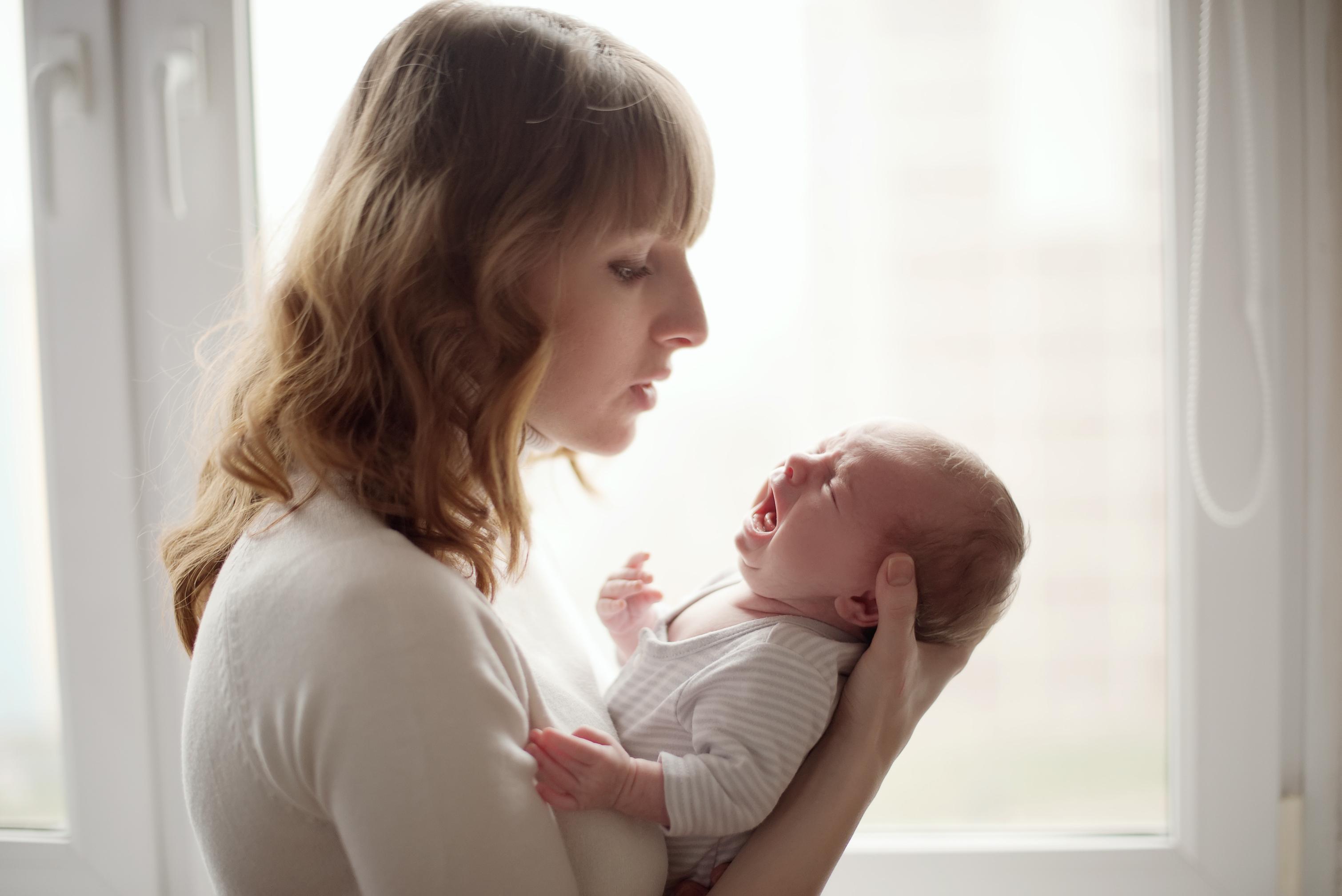 Madre intentando calmar el llanto de su bebé de alta demanda