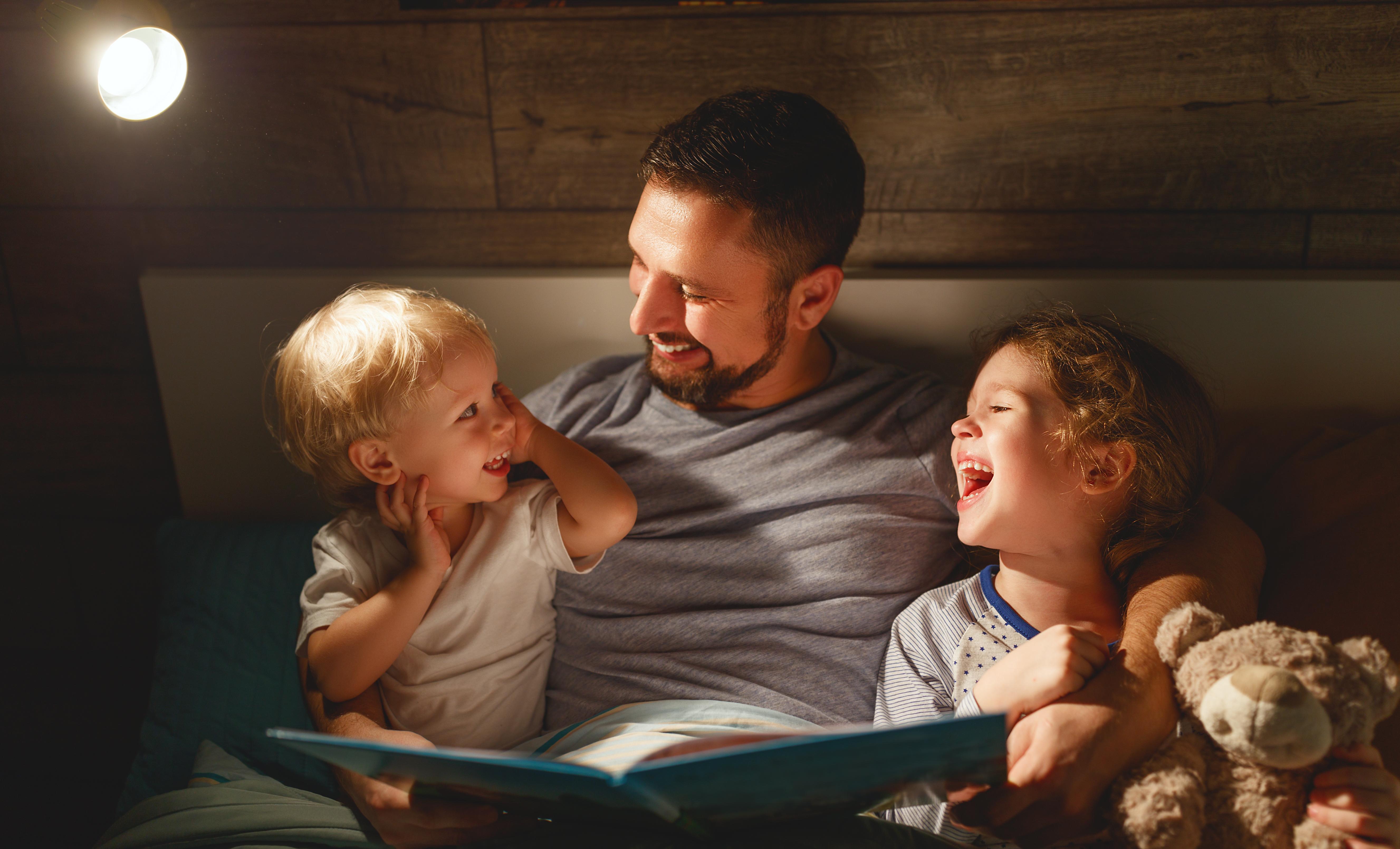 Padre contando un cuento en la cama a sus hijos