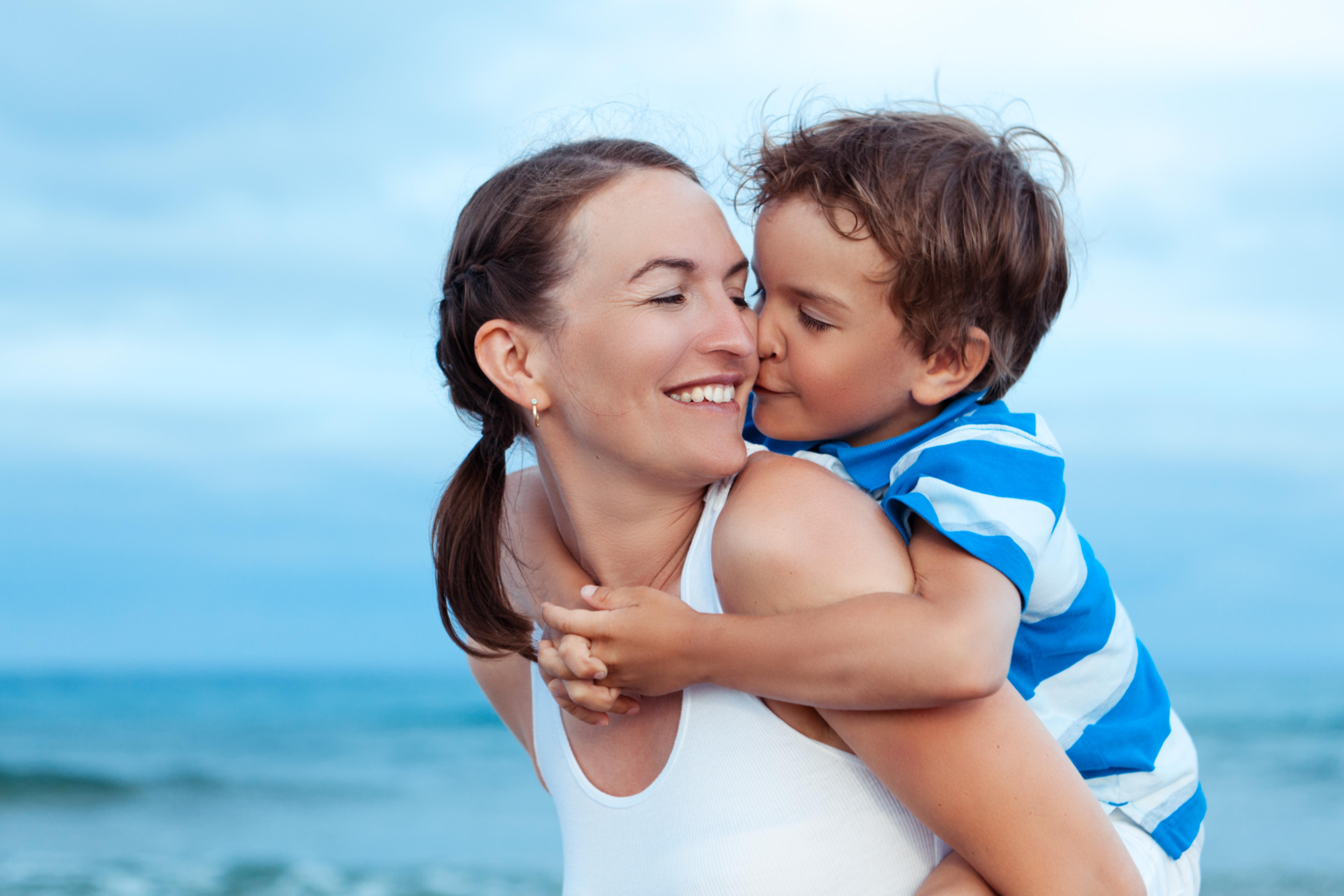 Madre llevando a caballito a su hijo