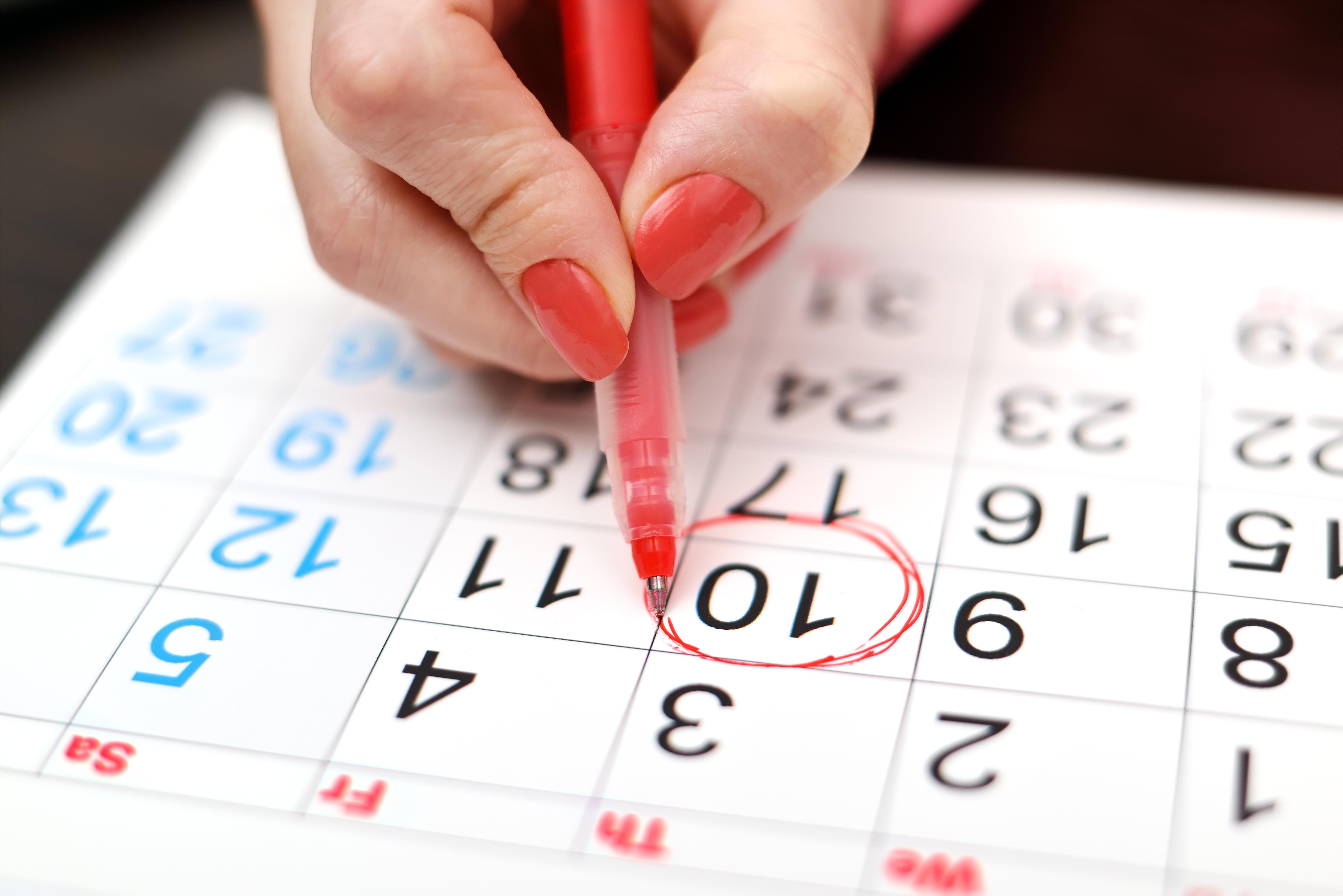 Mano de mujer marcando un día en el calendario con un rotulador rojo