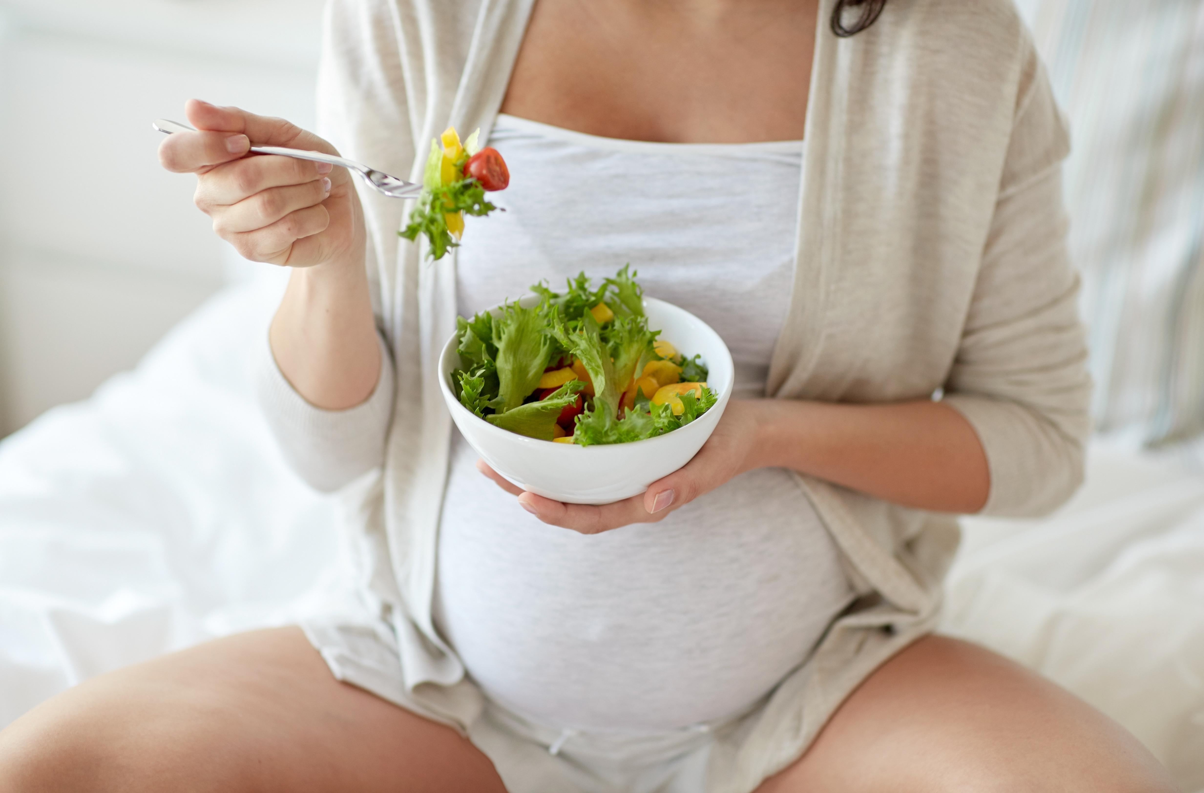 Mujer embarazada comiendo una ensalada