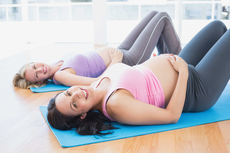 Dos mujeres embarazadas tumbadas haciendo ejercicios de Kegel