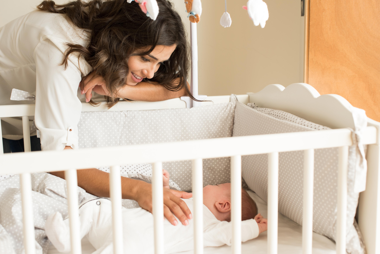 Madre mirando a su bebé mientras duerme en la cuna