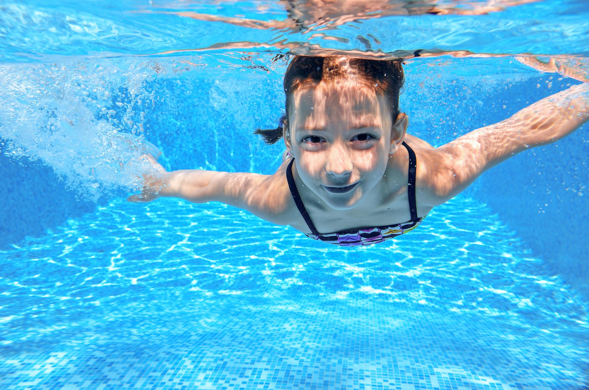 Niña buceando en una piscina