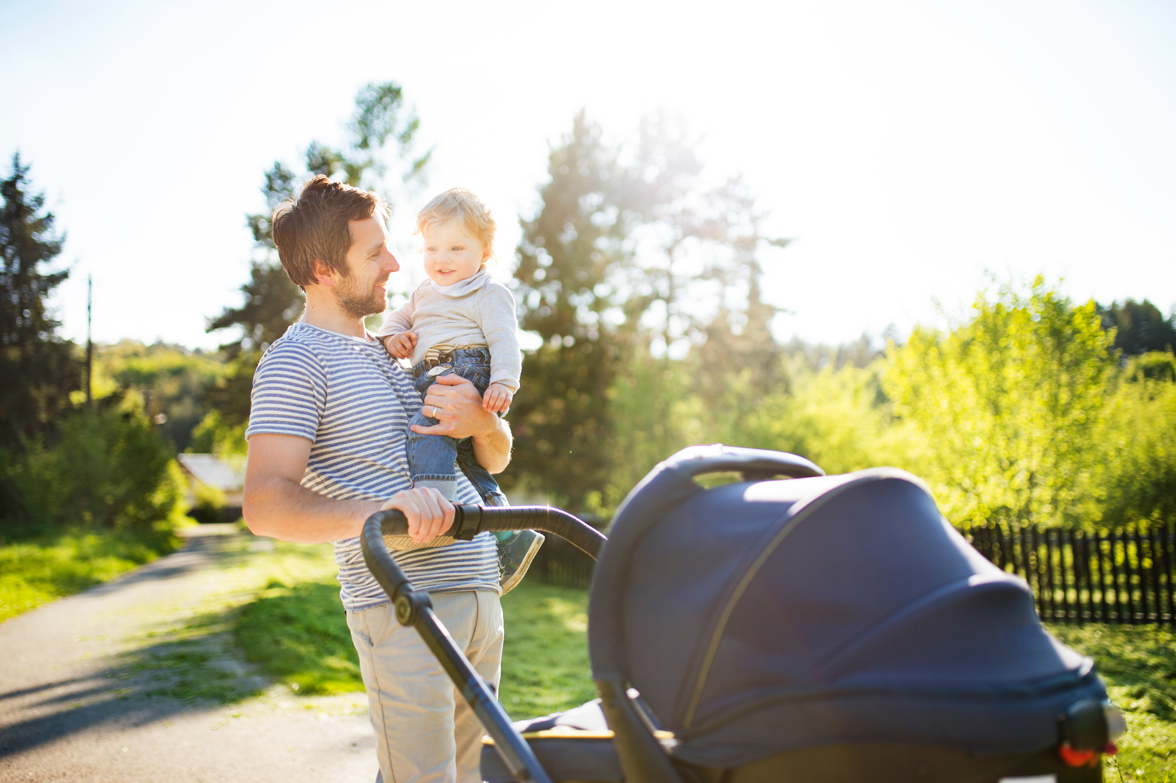 Padre con bebé en brazos en el parque llevando el carrito