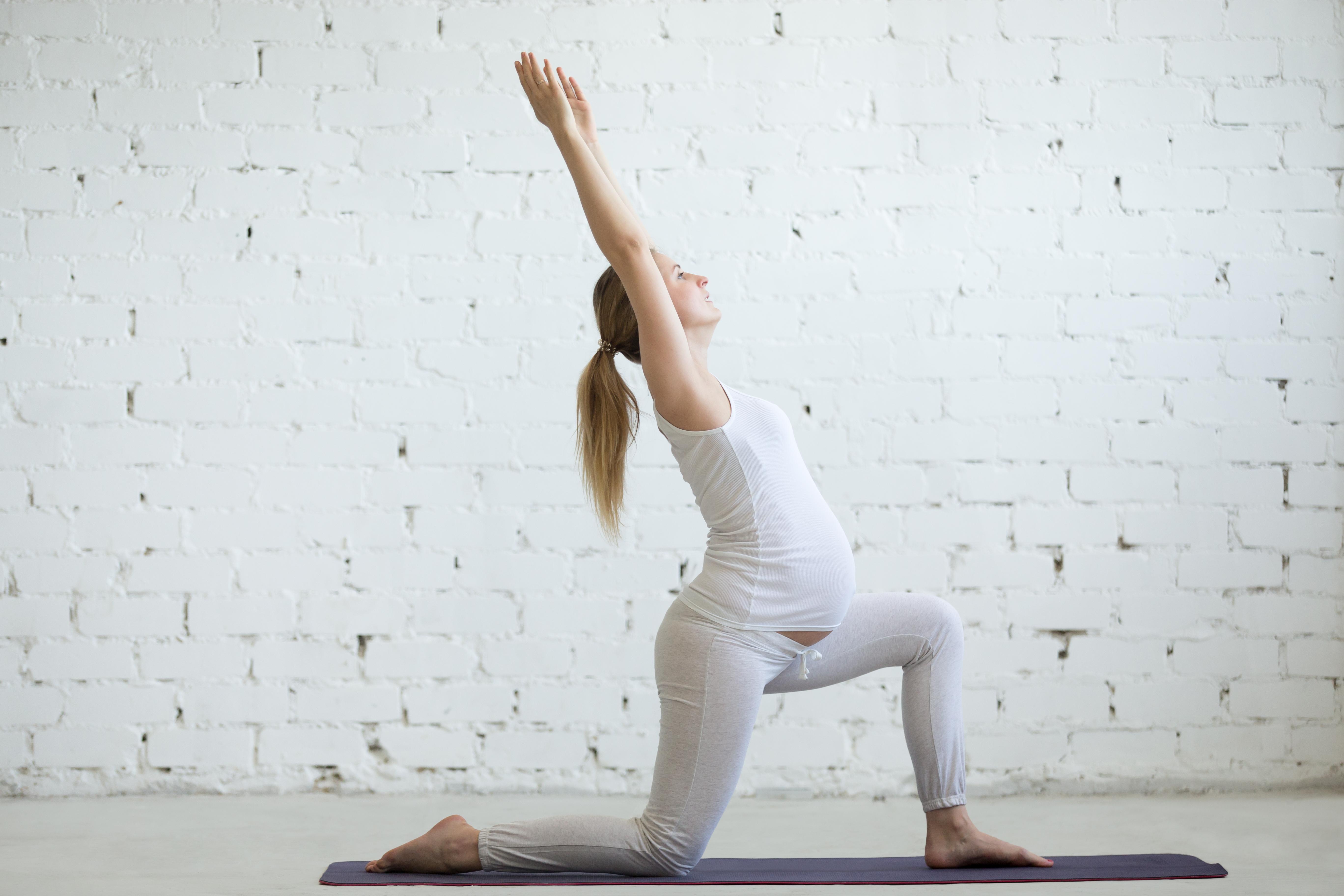 Mujer embarazada realizando una postura de yoga