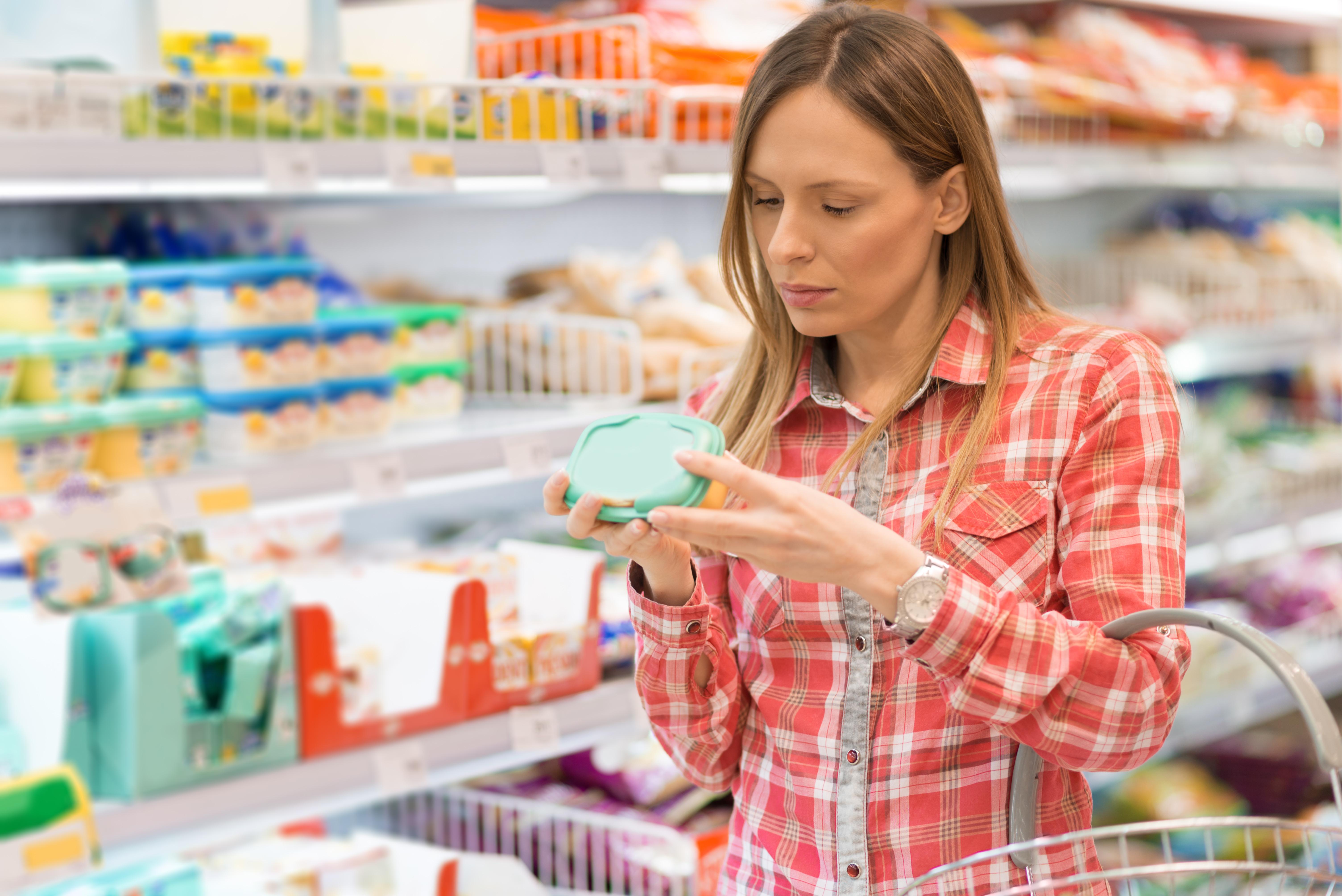 Mujer en el supermercado leyendo la etiqueta de un producto