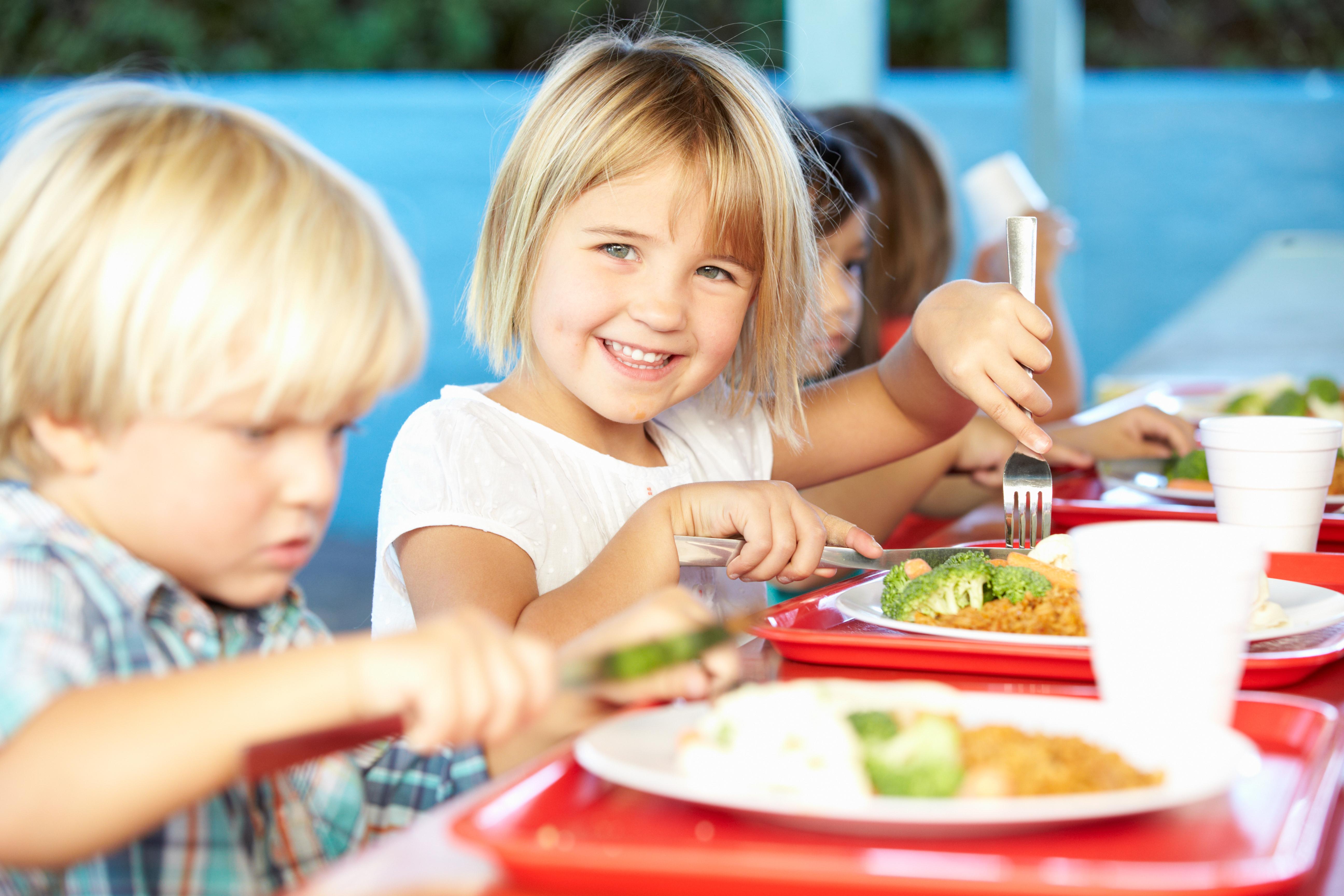 Grupo de niños comiendo en el comedor del colegio