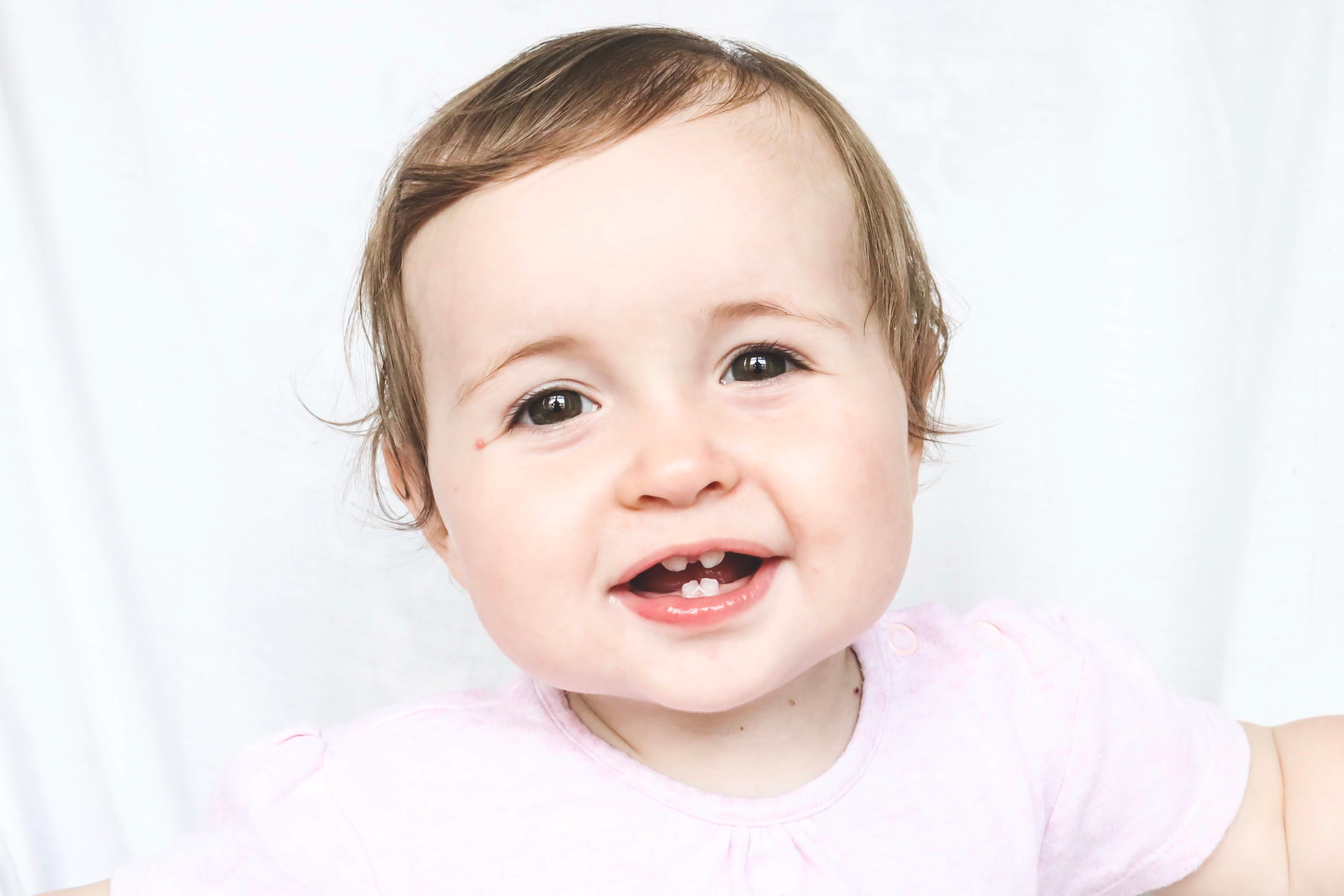 Bebé sonriente mostrando cuatro dientes de leche
