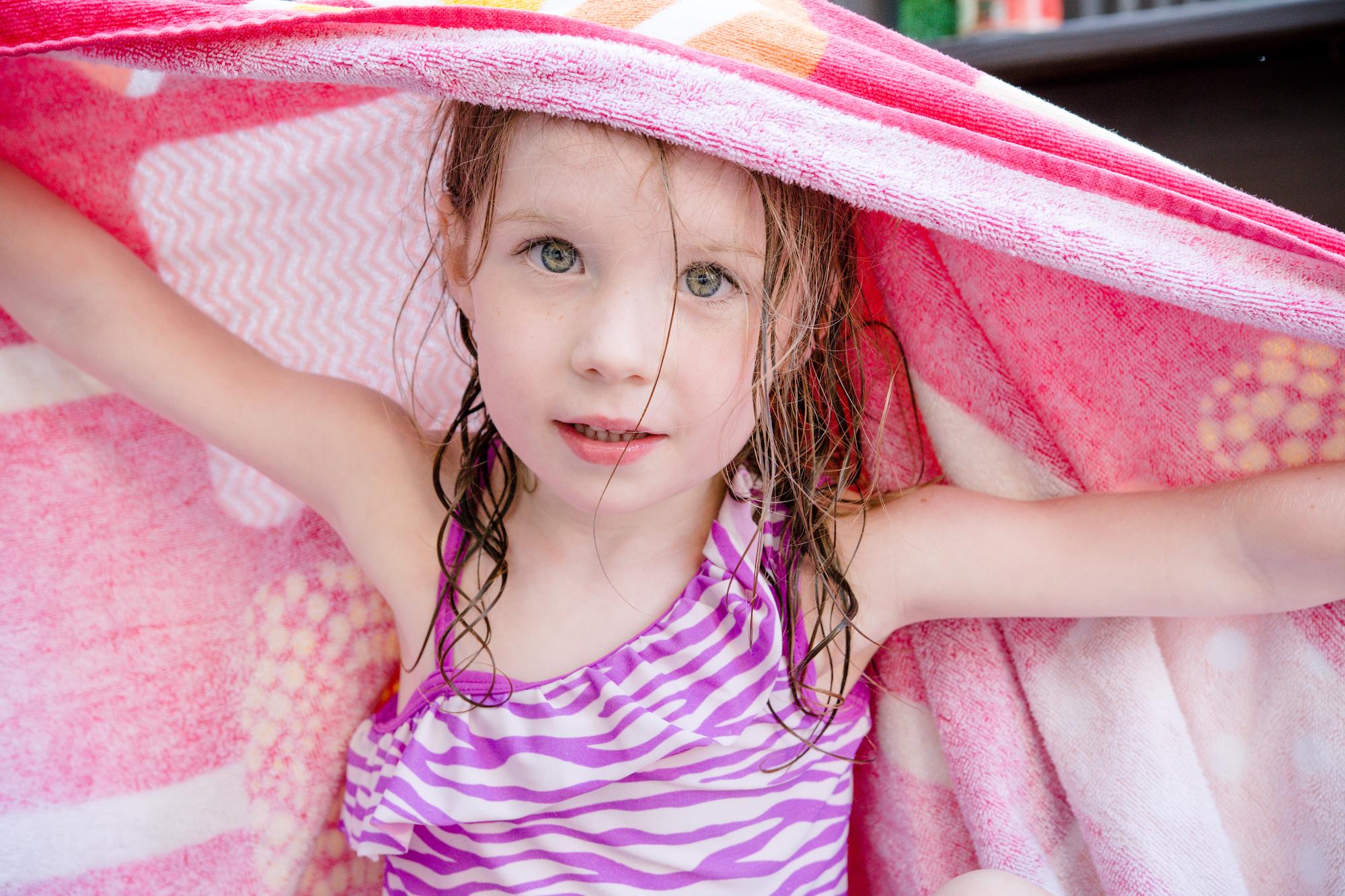 Niña secándose con una toalla en la piscina