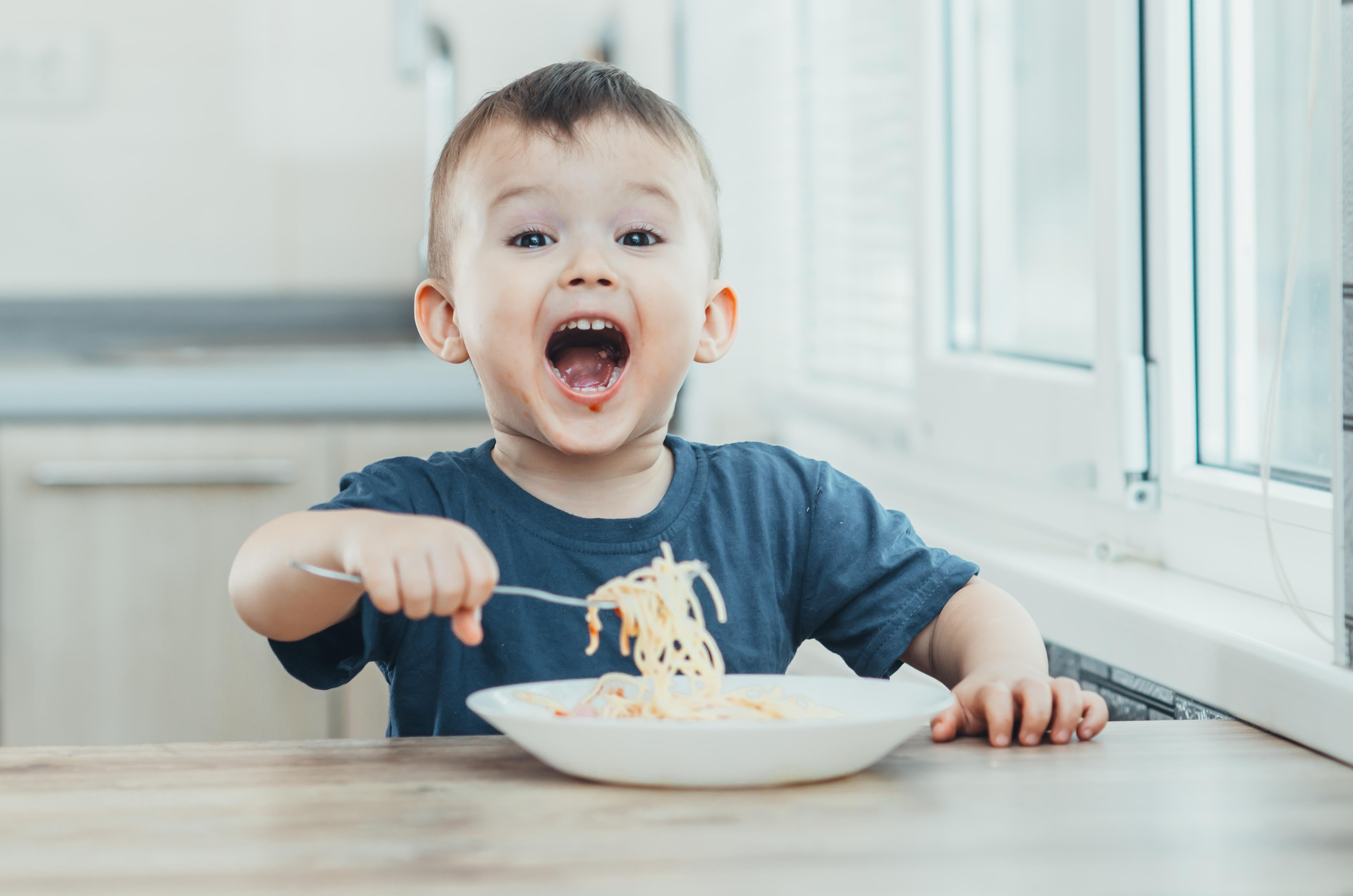 Niño de 2 años comiendo espagueti