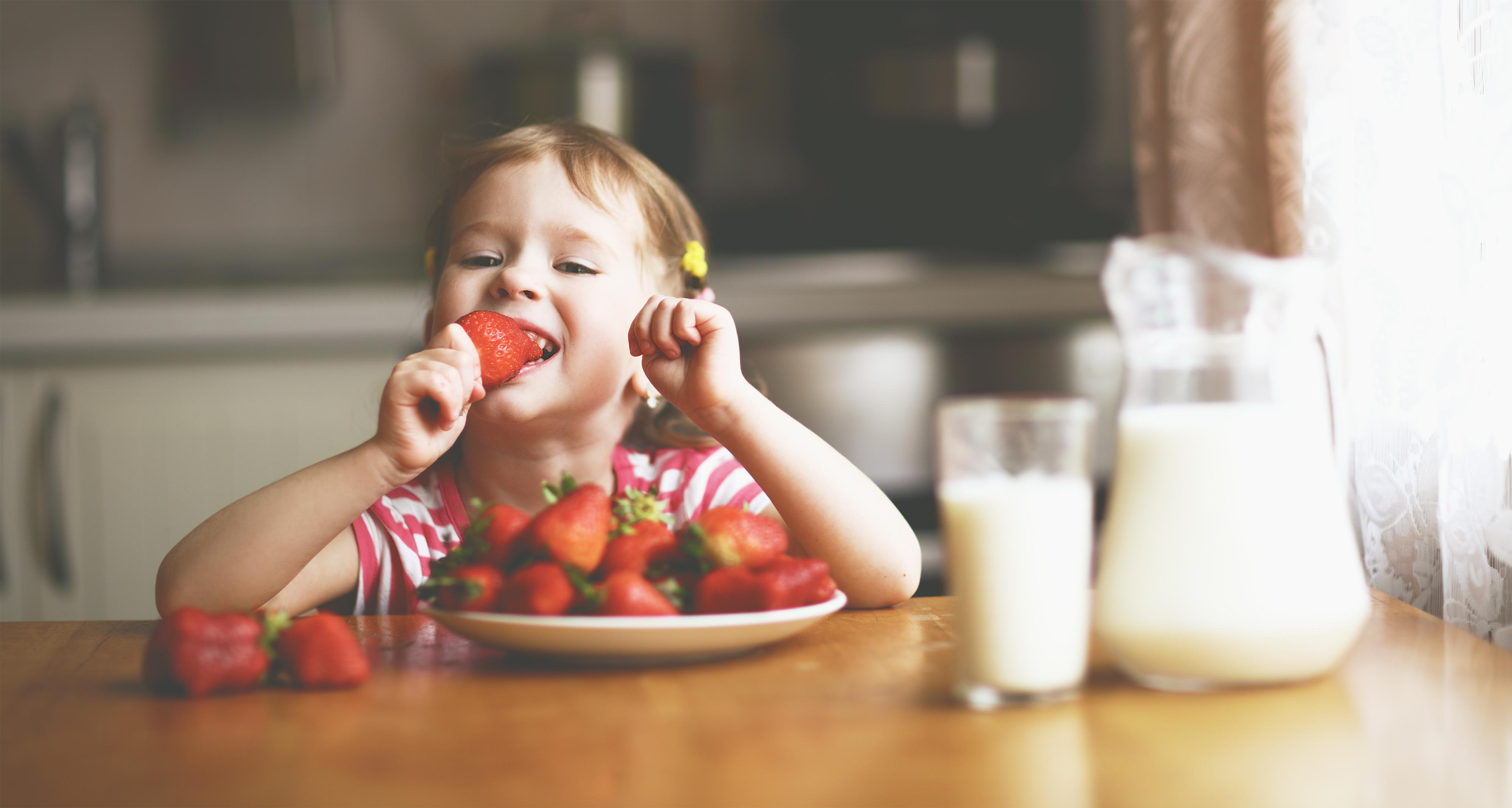 Niña de 2 años comiendo fresas