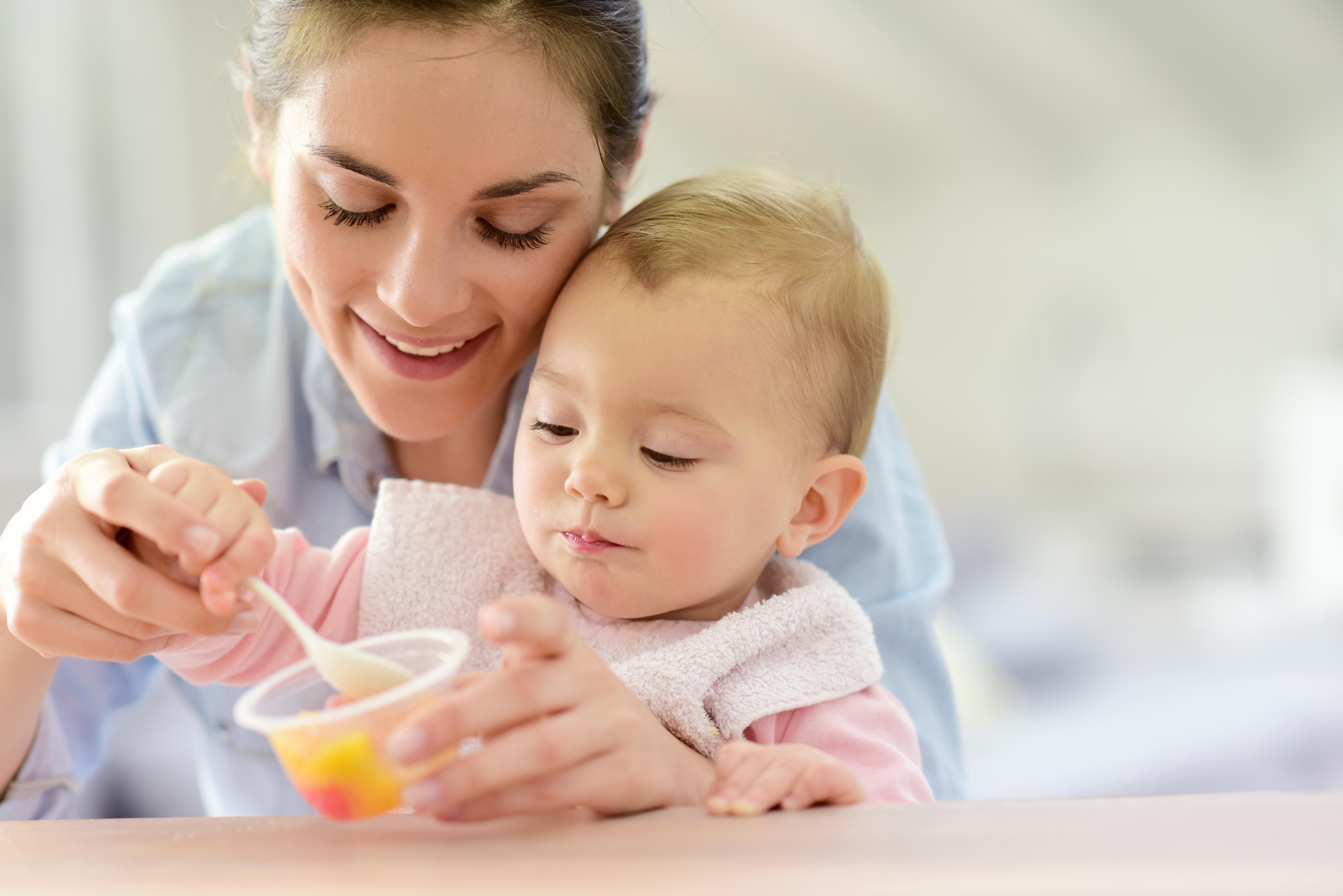 Madre dando de comer a su bebé