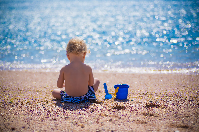 Niño jugando en la playa bajo el sol de espaldas