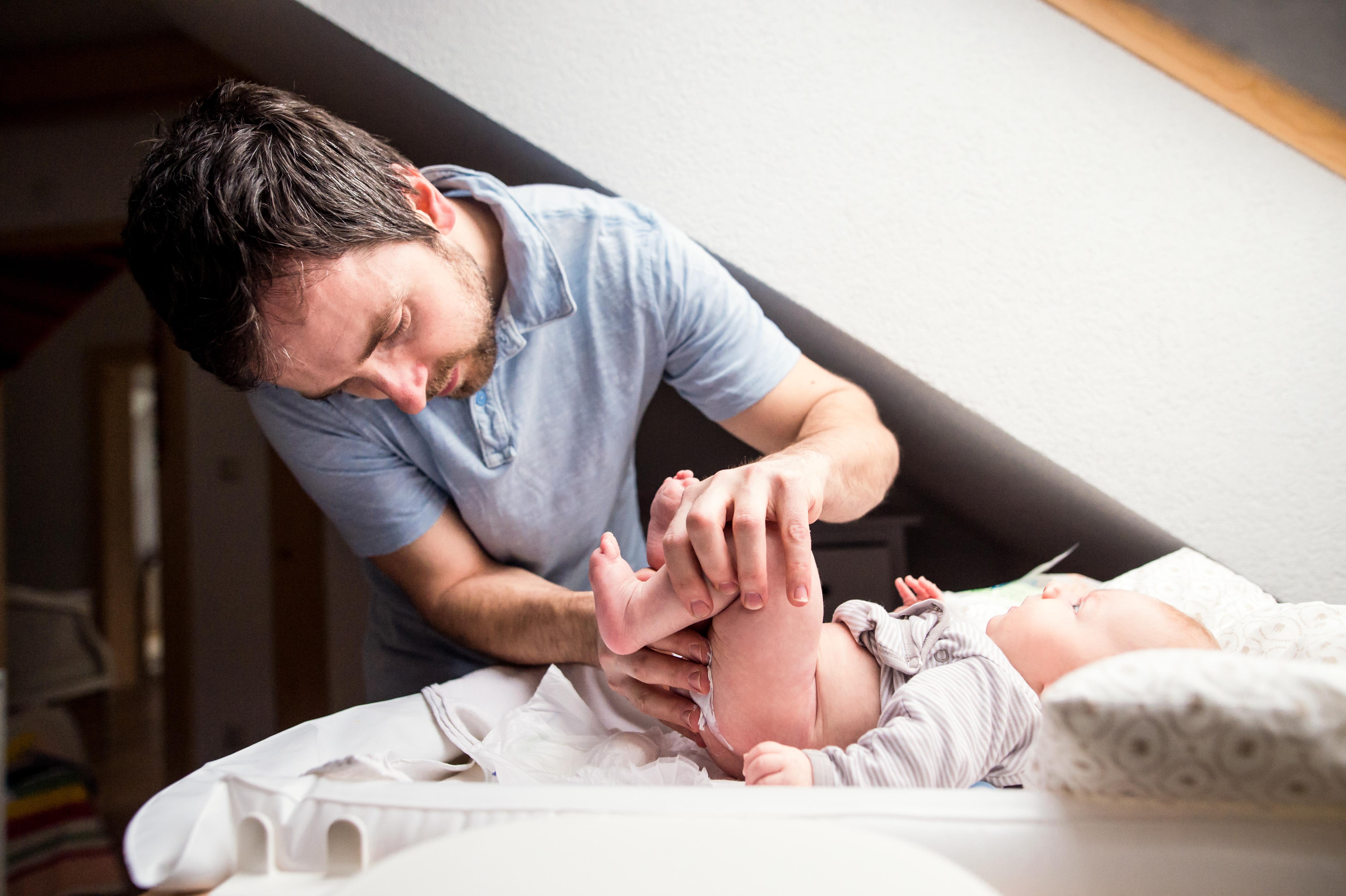 Hombre cambiando el pañal a su bebé