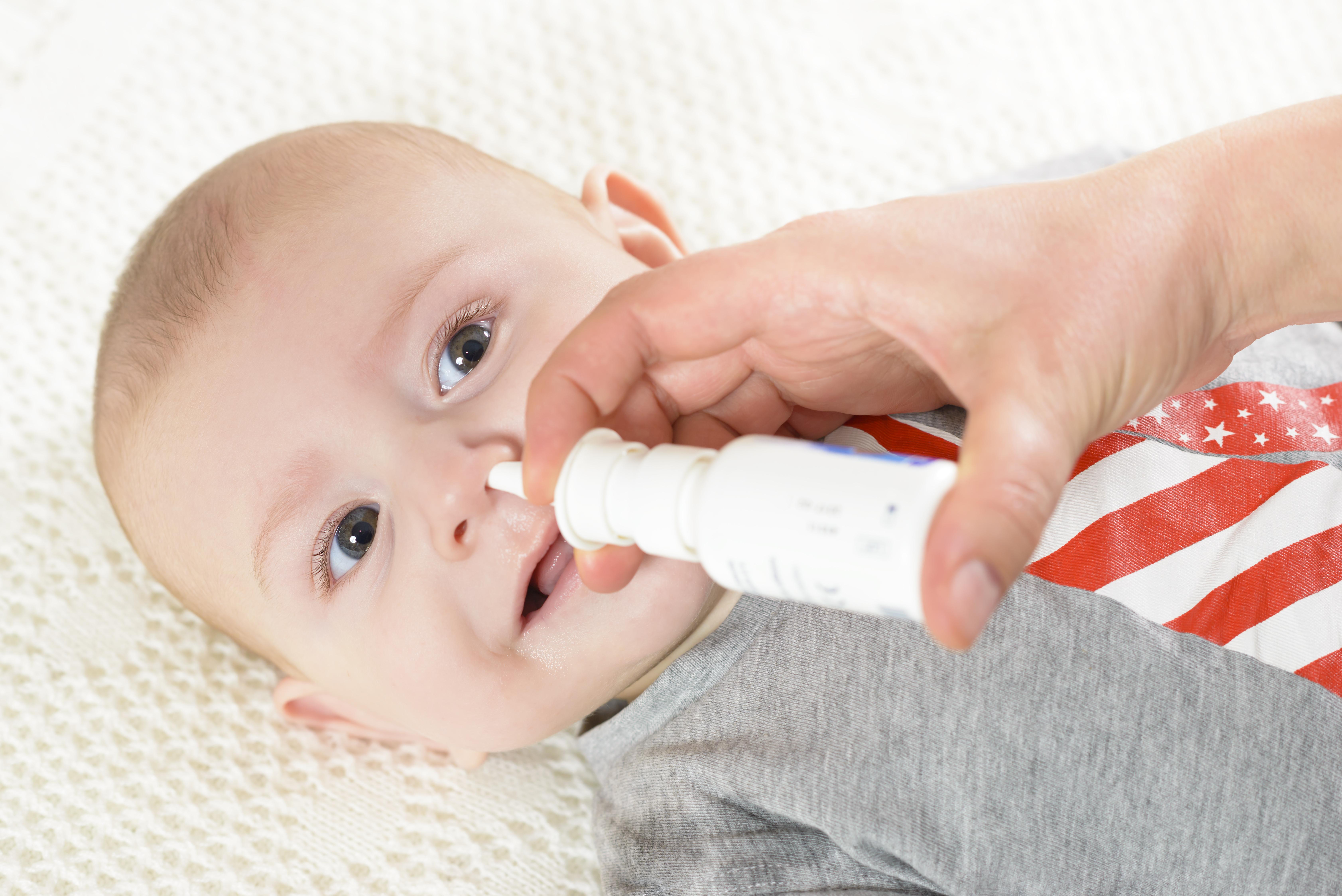 Bebé al que le limpian los mocos con suero