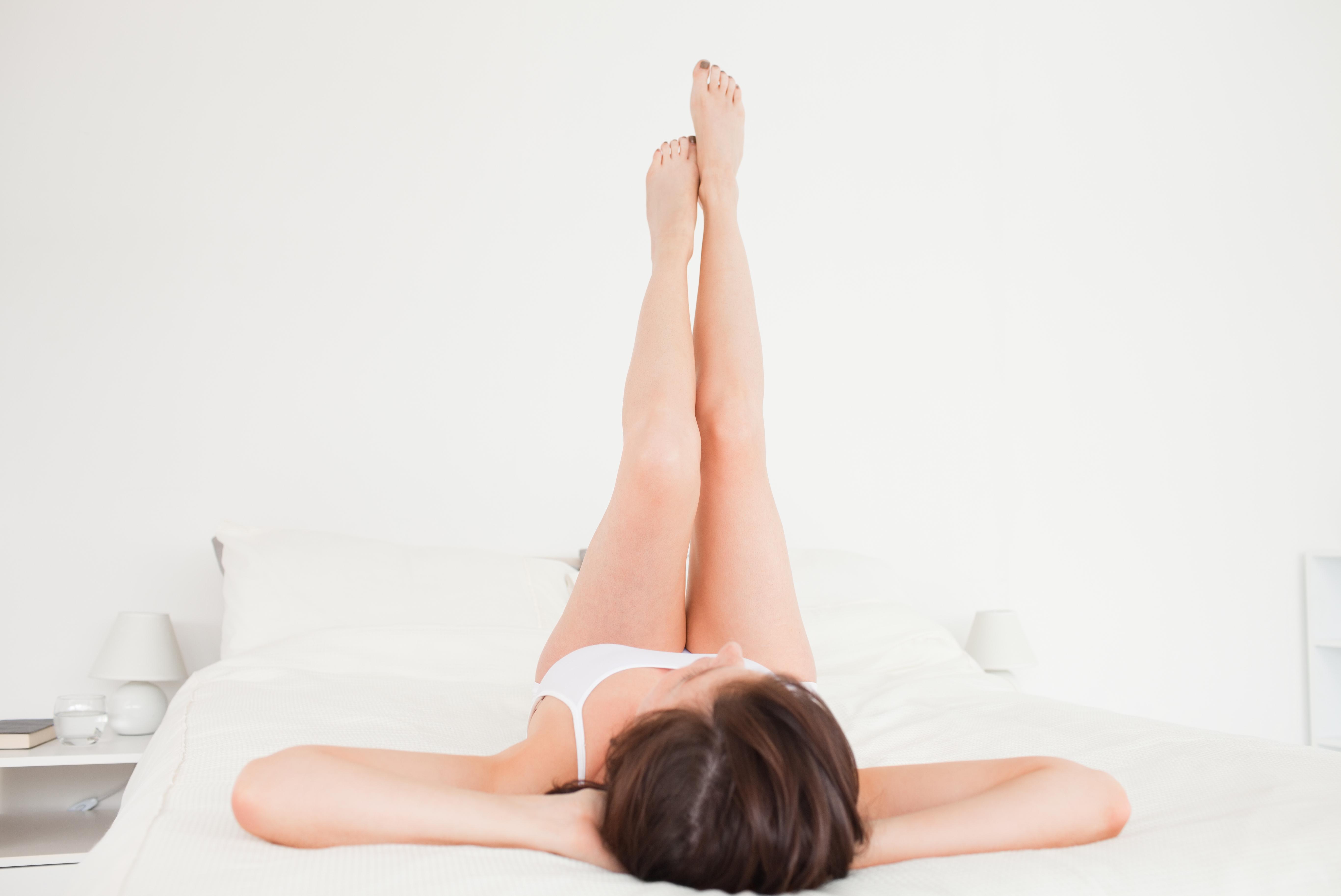 Mujer tumbada en la cama con las piernas en alto