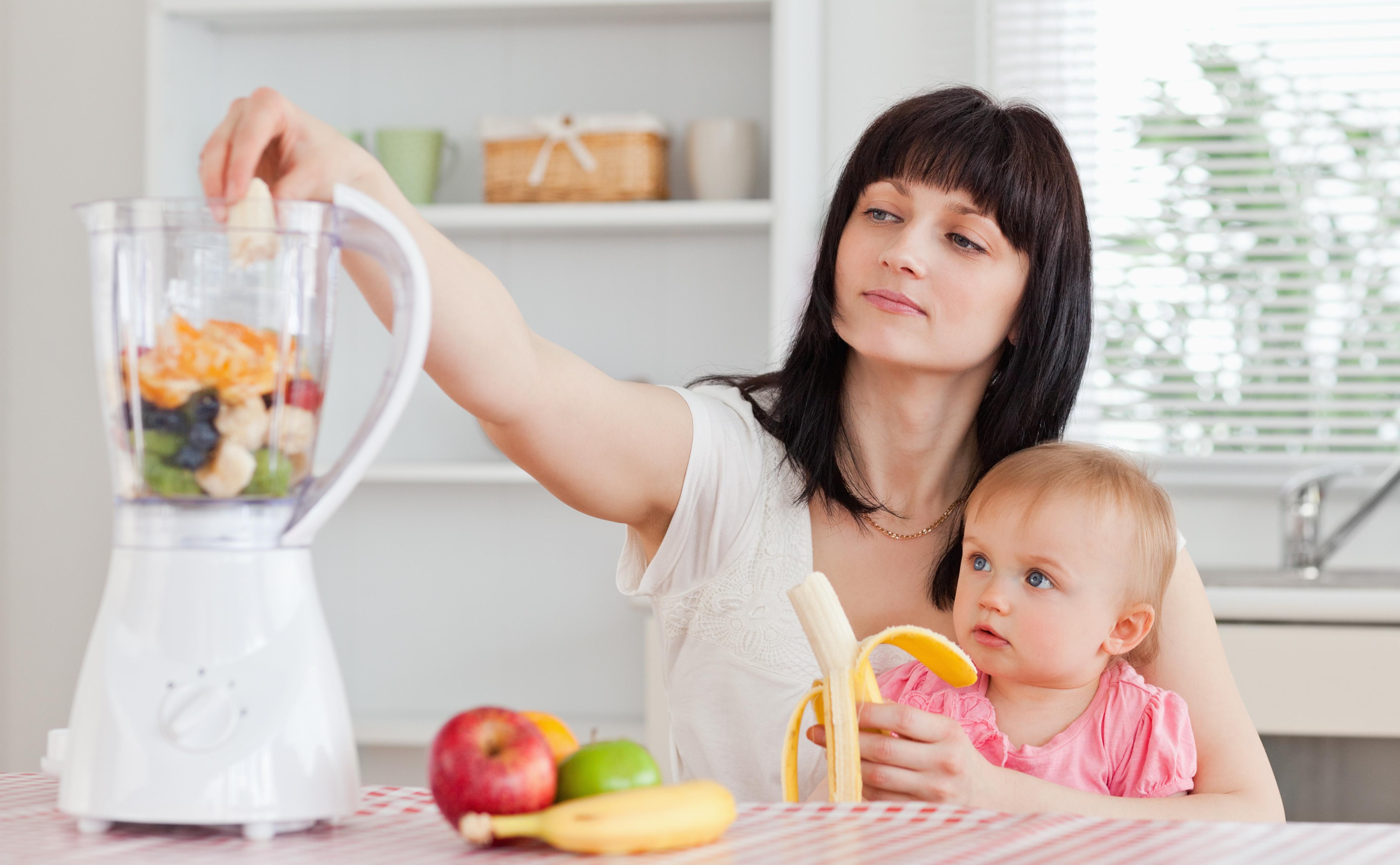 Madre preparando papilla de frutas con su bebé