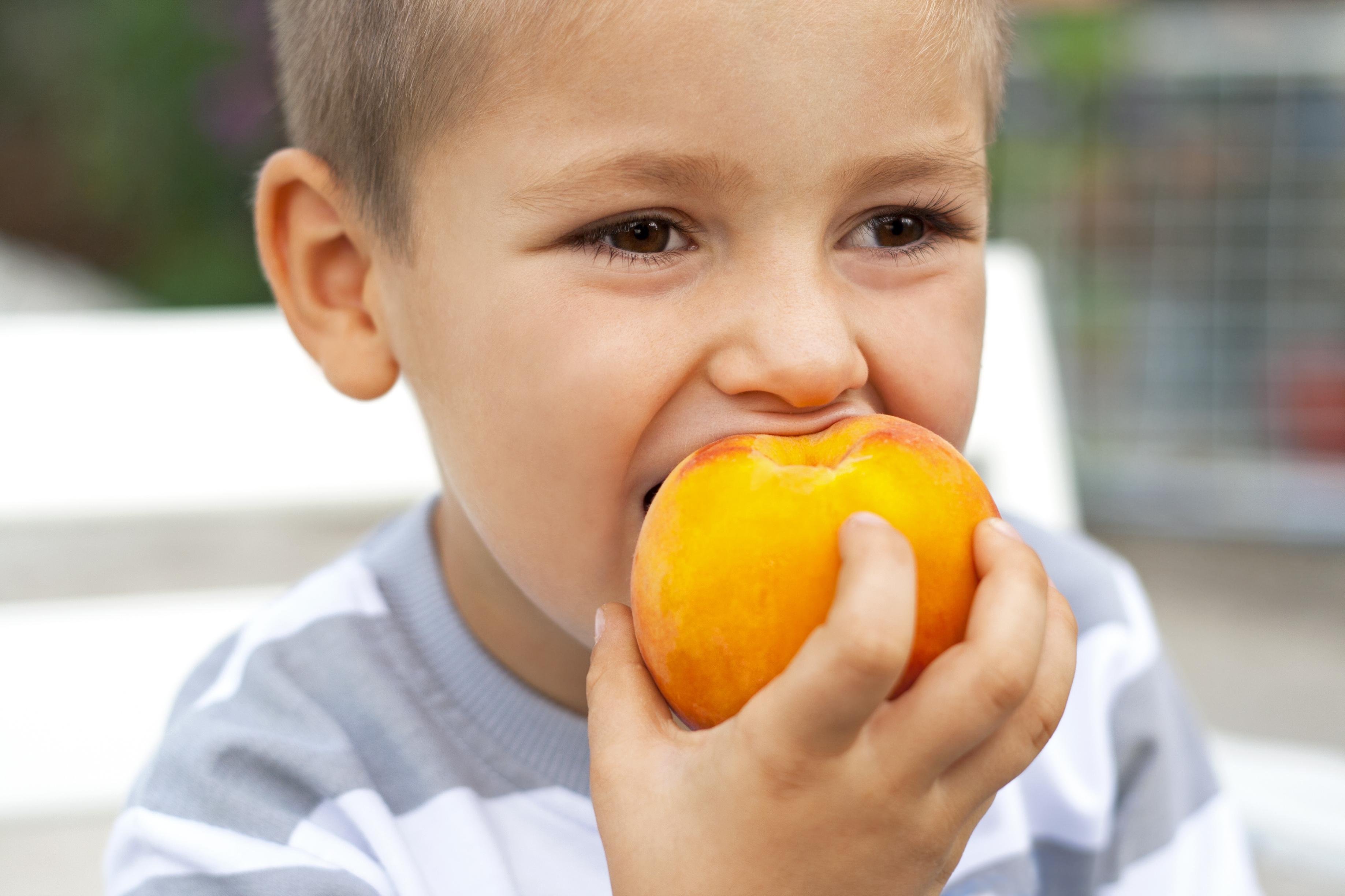 Niño comiendo un melocotón
